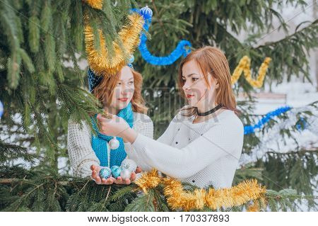 Girl decorate the Christmas tree in the park, outdoor winter cold day