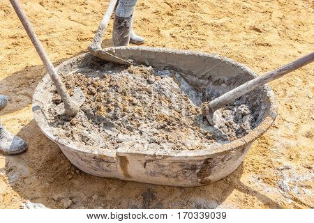 Three concrete workers mixing the cement and sand in grunge steel salver building construction site.