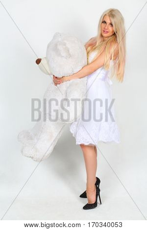 Woman in white dress stands with big toy bear in white studio