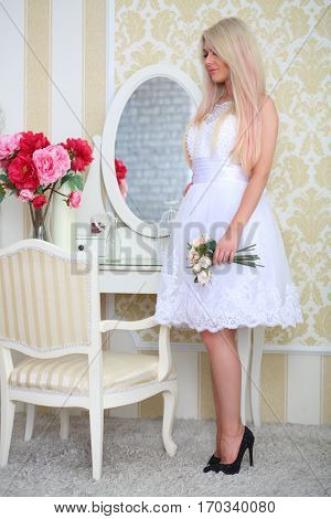 Woman in white dress holds flowers in cozy light room, full body