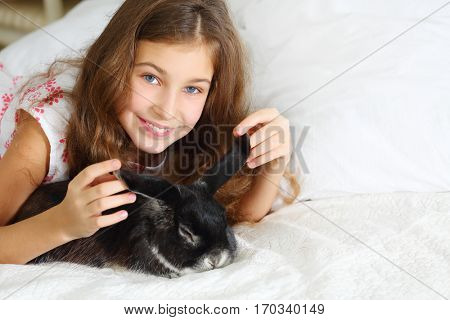 Happy smiling girl in dress poses with funny rabbit on white bed in room