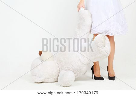Woman in white dress holds legs of big toy bear in white studio, noface
