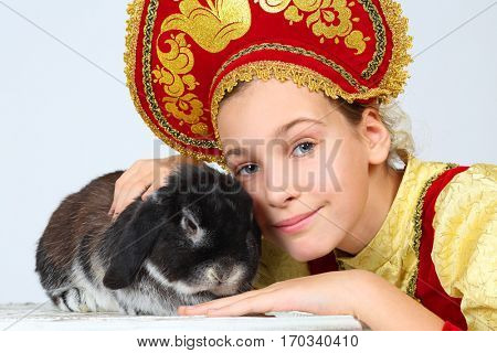 Pretty girl in red russian folk costume poses with rabit in white studio