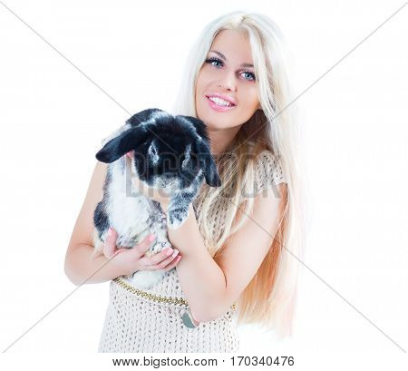 Cute blonde in dress holds funny black rabbit isolated on white