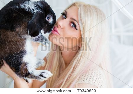 Pretty young blonde kisses fluffy black rabbit on white bed in room