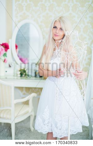 Young woman in white dress touches white hanger in cozy light room