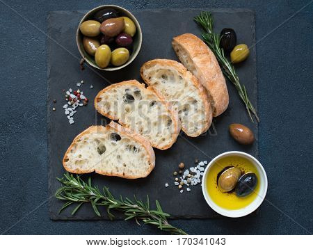 Italian food ingredients background with Sliced bread Ciabatta, olive oil, olives and rosemary on dark stone slate. Top view