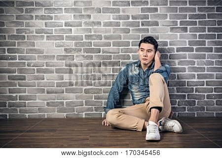 young Asian man sit on ground feel lonely