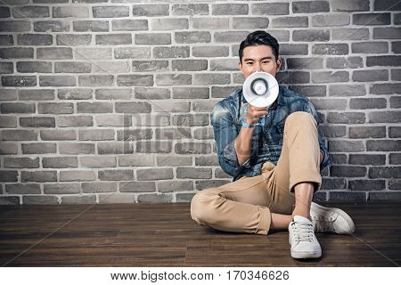 young Asian man sit on ground and using bullhorn