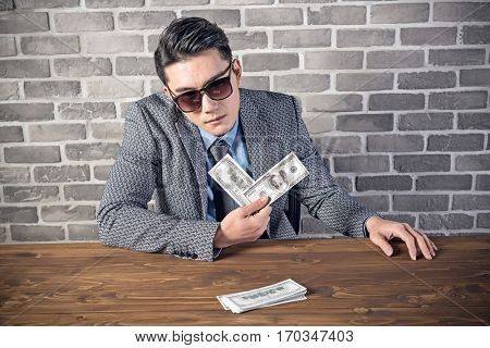 greedy businessman put the cash on desk and look at you