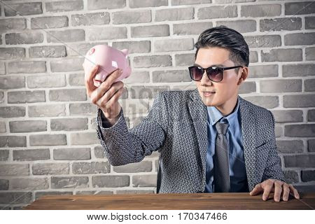 greedy businessman look at the pink pig bank