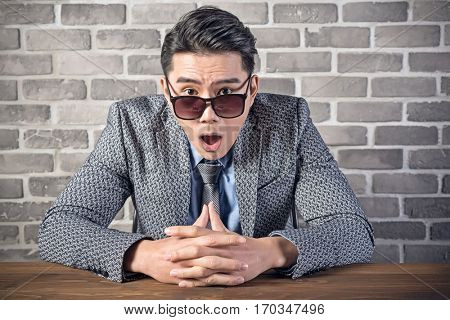 surprised fashionable young businessman sit and look at you