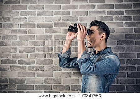 Asian young man hold a binoculars
