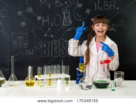schoolgirl in chemistry lab in white gown pointing at formula on blackboard near table with reagents