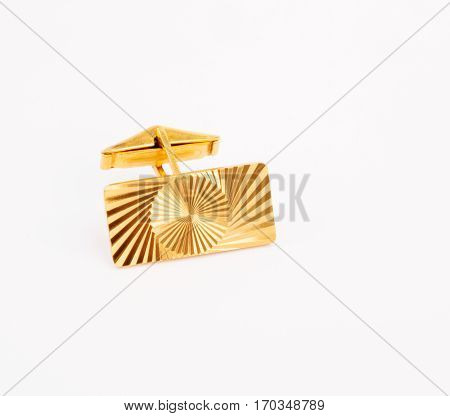 Old gold plated cufflink for shirt sleeves closeup isolated on white background