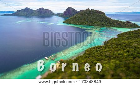 Borneo quote concept with Tropical paradise island with bright smooth mirror sand & crystal clear water with rocky shore in the island of Semporna, Borneo, ideal for print card and poster design.