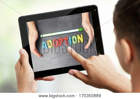 Adoption concept. Male hands with tablet and search box on screen