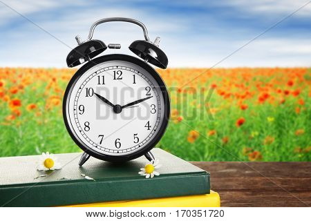 Alarm clock with books and flowers on wooden table against landscape background. Time change concept