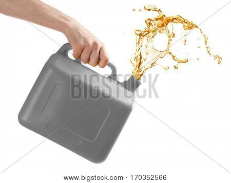 Man pouring oil out of plastic canister on white background