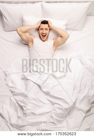 Frustrated guy lying in bed and screaming