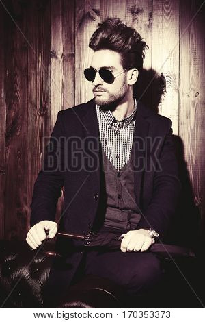 Portrait of a well-dressed imposing man in sunglasses. Men's beauty, fashion. Hair styling, barbershop.