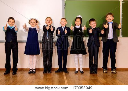 Group of happy classmates in school uniform posing together at a classroom. Education.