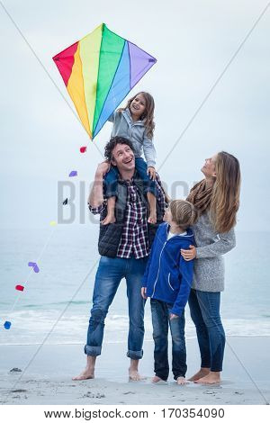 Full length of cheerful family with kite standing at sea shore