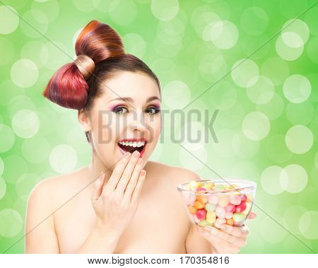 Beautiful smiling girl eating sweets from a bowl on bubble background.
