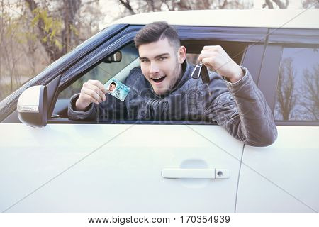 Man with driving license and key in car