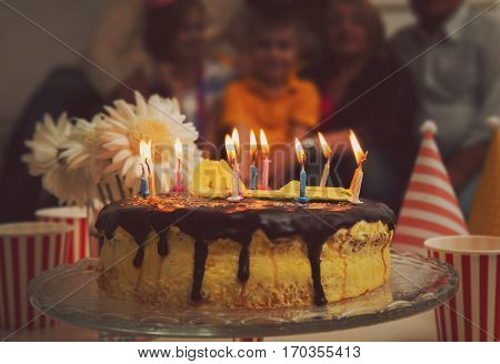 Birthday cake with alight candles and big family on background
