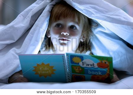Cute little girl reading book in bed under blanket