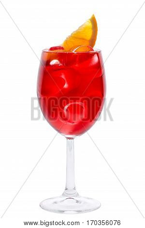 Wineglass with red fruit coctail decorated with lemon slice and ie close-up on the white background