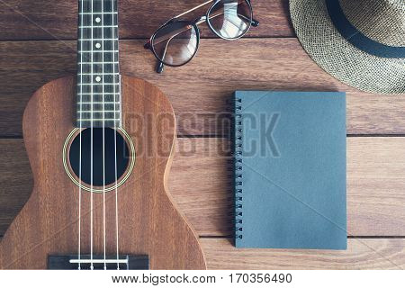 Ukulele guitar with notebook on wooden table