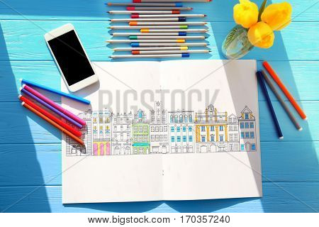 Colouring book, pencils and felt pens on wooden table