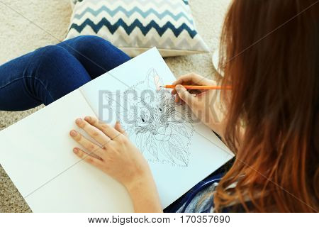 Young woman sitting with coloring pictures for adults