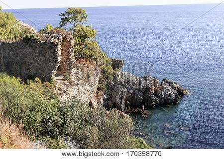Sea bay with remains of ancient city Iotape or Aytab with rocks and pine tress