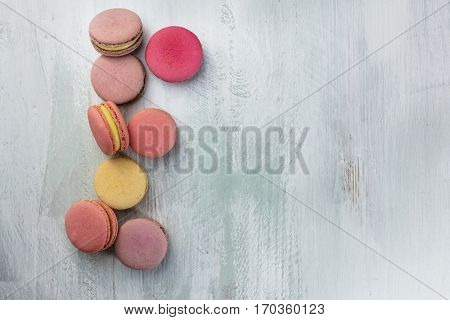 A photo of various macarons, shot from above on a teal background texture, with a place for text