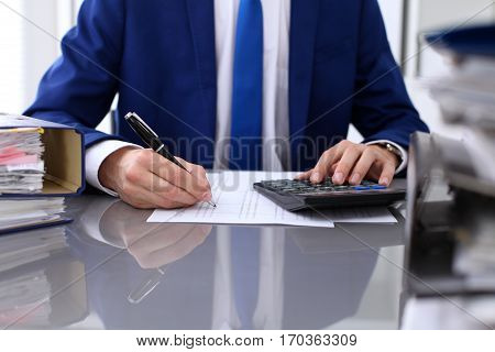 Close up view of bookkeeper or financial inspector hands making report calculating or checking balance. Internal Revenue Service inspector checking financial document.