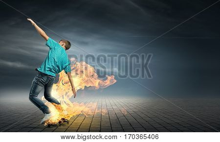 Skater boy riding on his skateboard burning in fire