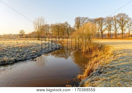 Picturesque rural winter landscape with a thin layer of snow and hoarfrost and a bent stream in low early morning sunlight.