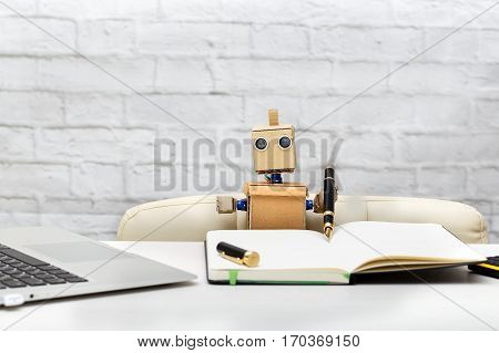 robot is sitting at a table and writes a pen in a notebook