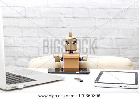 Robot and his workplace: laptop phone tablet