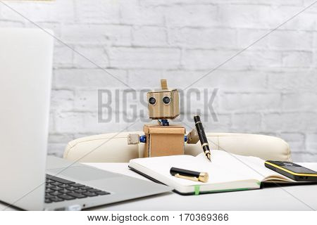 Robot working at a computer; workplace, notebook, phone