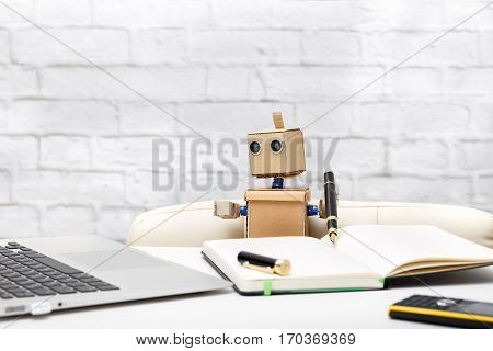 robot is sitting at a table holding a pen and looking at a laptop