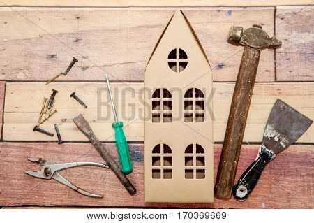 Hammer, putty knife, screwdriver and tools for repair and construction and a two-story cardboard house on the wooden background. Concept of repair and construction