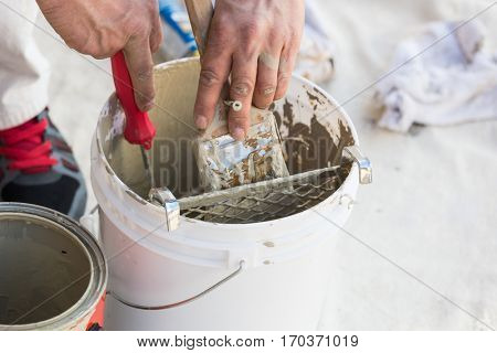 Professional Painter Loading Paint Onto His Brush From A Bucket.