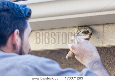 Professional Painter Using A Brush to Paint House Fascia Under Rain Gutter.
