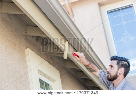 Professional Painter Using A Small Roller to Paint House Fascia.