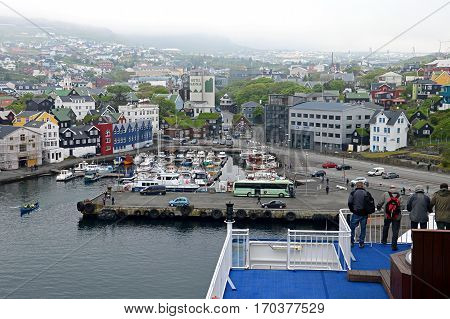 Torshavn, Faroe Islands - June 5, 2014: View over Torshavn, the capital of the Faroe Islands. Men standing at the railing above the small harbor and look over the city. The upper part of the city is shrouded in a dense fog.