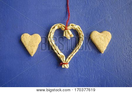 Two cookies in the shape of hearts on a blue background and hanging heart made of straw. Love concept background. February 14 holidays. Happy valentines day celebration. Straw heart.
